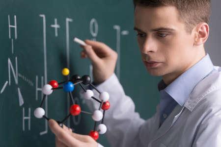 genetically modified: uomo che tiene cellulare e di scrivere sulla lavagna. Colture cellulari test per testare i prodotti geneticamente modificati