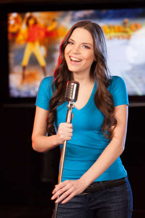 Beautiful brunette with microphone standing in bar. waist up portrait of smiling brunette singing  photo