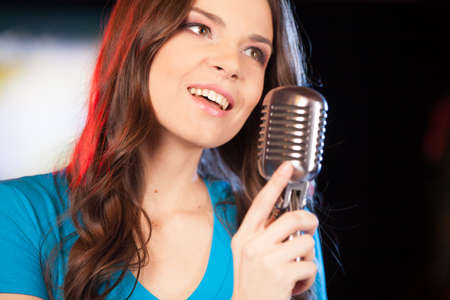 Beautiful girl with microphone standing in bar. closeup of beautiful brunette girl singing with microphone.  photo