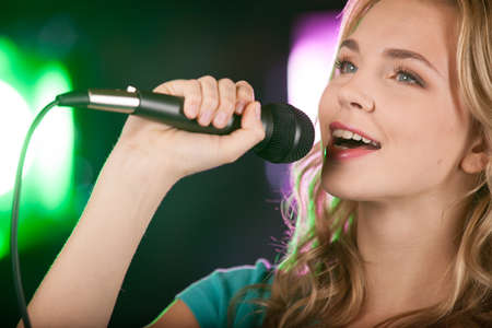 Beautiful girl with microphone standing in bar. closeup of beautiful blond girl singing with microphone.  photo