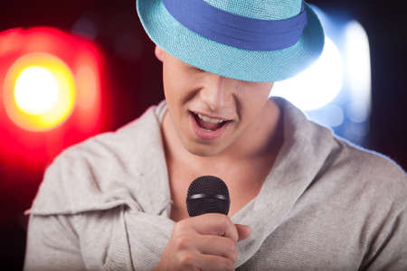 kareoke: Portrait of male singer wearing blue hat. handsome man singing into microphone alone Stock Photo