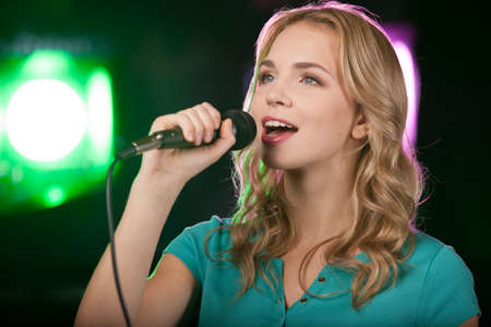Portrait of young beautiful girl singing. closeup of blond girl holding mic photo