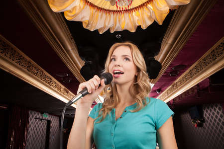 Beautiful blond with microphone standing and singing. young woman holding mic and smiling photo