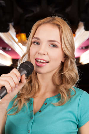 Beautiful blond with microphone standing and singing. closeup of young woman holding mic and smiling photo