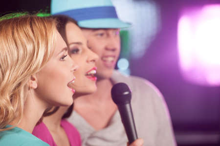 group shot: Happy three friends singing in microphones. two women and man having fun isolated in bar  Stock Photo