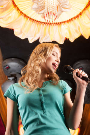 Beautiful blond with microphone standing in bar. waist up portrait of smiling brunette singing  photo