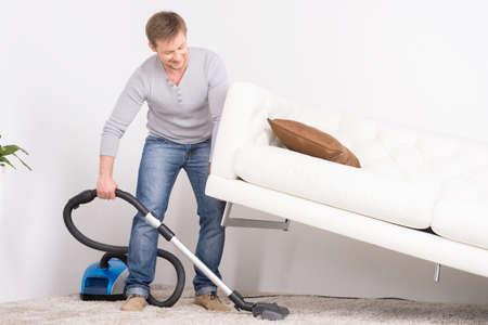 掃除機で男は家の仕事。男性真空洗浄のリビング ルームでソファを持ち上げた。