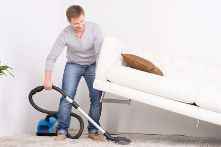 man does house work with vacuum cleaner. Men lifted sofa in living room, vacuum cleaning.