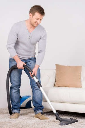 man does house work with vacuum cleaner. Men in living room vacuum cleaning.  Stock Photo