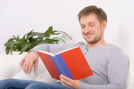 Closeup portrait of young, handsome man reading book. man reading book sitting on sofa photo