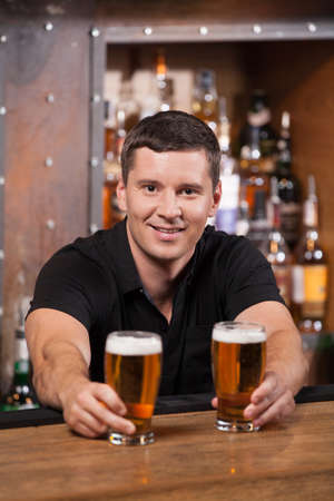 Bartender serving two glasses of beer. adult man holding beer glasses and smiling photo