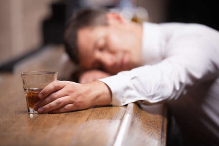 brunett: Drunk and unconscious guy lying on counter. man sleeping after hard day in bar