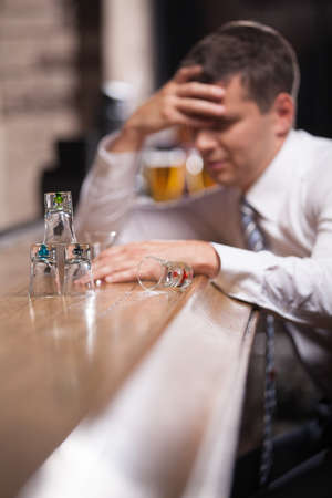 Pensive businessman having drink in classy bar. young man looking at glasses pyramid photo