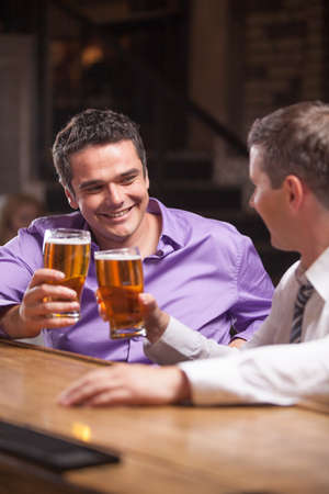 friends drinking: closeup portrait of two young man talking at counter. two friends sitting in bar and drinking beer