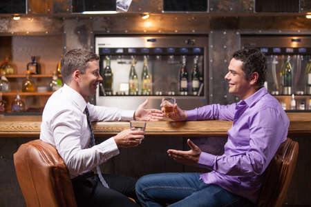 after work: two young man talking at counter. two friends sitting in bar and drinking whisky