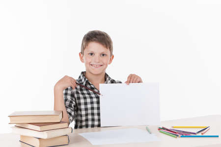cute boy sitting at table and writing. handsome little schoolboy showing white sheet photo