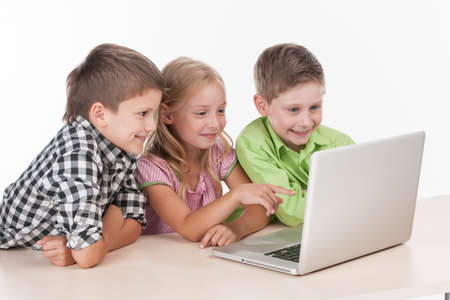 Three kids using computer on white background. nice children playing with laptop and smiling