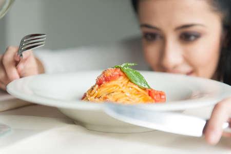 Close-up van de handen van de vrouw met vork en mes. jong meisje op zoek naar eten in restaurant Stockfoto