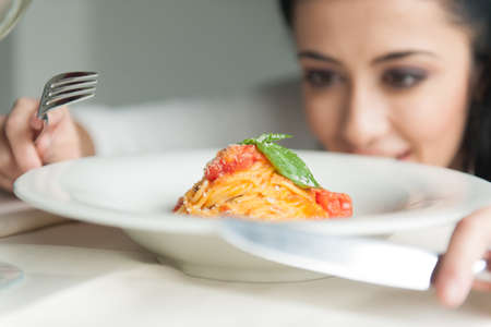 Closeup of woman's hands holding fork and knife. young girl looking at food in restaurant