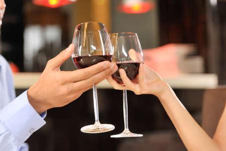 Twee mensen het roosteren met wijnglazen. jong koppel drinken van rode wijn in de bar Stockfoto