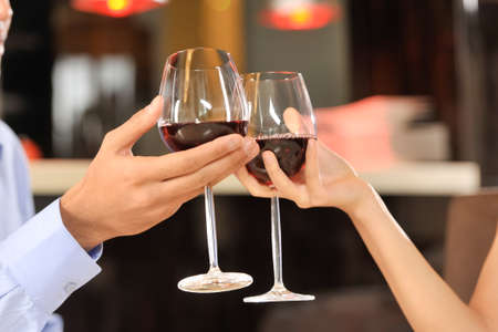objects drink: Two people toasting with wine glasses. young couple drinking red wine at bar