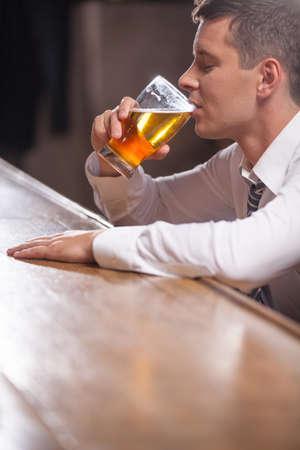 hombre tomando cerveza: Joven solitario beber solo en el pub. hombre sentado en el extremo de la barra del bar bebiendo una pinta de cerveza de barril