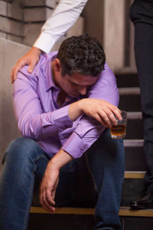 Handsome young man talking to drunk man sitting on stairs. closeup of guy drinking whisky and sleeping Stock Photo