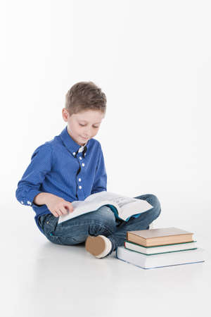 kids learning: Cute boy reading book isolated on white. boy holding book and reading near stack of books
