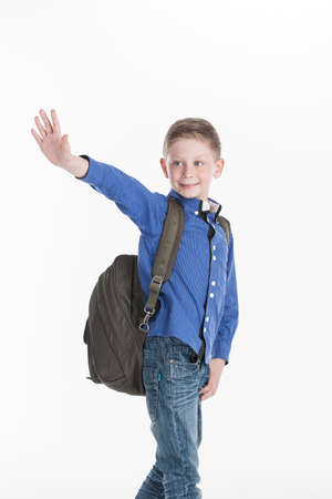 parting: boy standing and waving hand on white. cute school boy holding hands in pocket