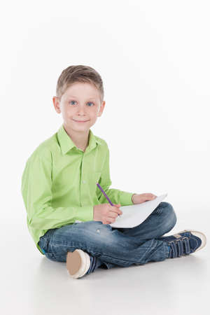siting: front view of little boy siting on floor. cute boy drawing and holding pencil