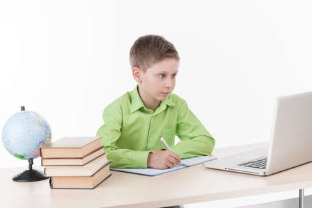 software portability: Happy little boy using laptop at table. cute schoolboy sitting at desk and writing in notebook