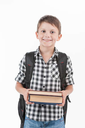 Happy schoolboy wearing backpack and holding books. cute schoolboy standing isolated on white background photo