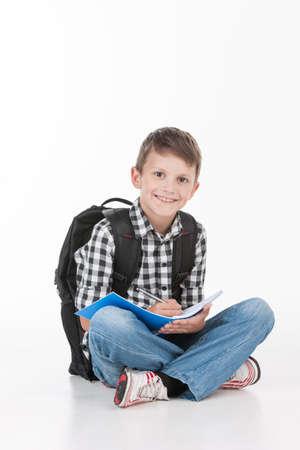niño con mochila: Colegial feliz con el cuaderno aislado en el fondo blanco. Muchacho lindo que se sienta en el piso y la escritura
