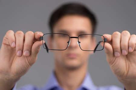 examen de la vista: hombre que llevaba gafas para mejorar la visi�n. hombre con gafas negras sobre fondo gris. Foto de archivo