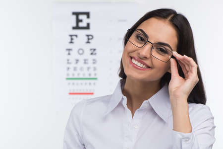 Portrait of happy smiling young woman. girl holding glasses in eye doctor, isolated over white background  Stockfoto