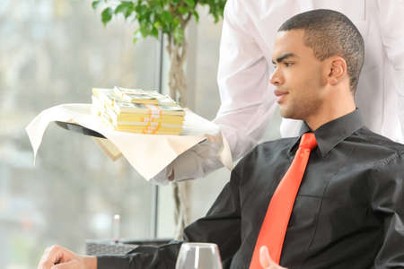 man sitting in restaurant and looking at money. waiter holding tray full of money photo