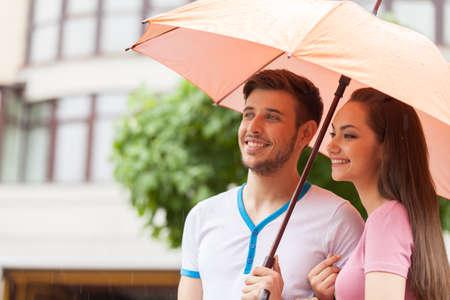 sotto la pioggia: Ritratto di donna e uomo in piedi sotto l'ombrello. bella coppia a piedi sotto la pioggia e sorridente