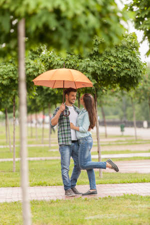 young couple standing under umbrella in park. blurred view of tree with focus on man huging woman photo