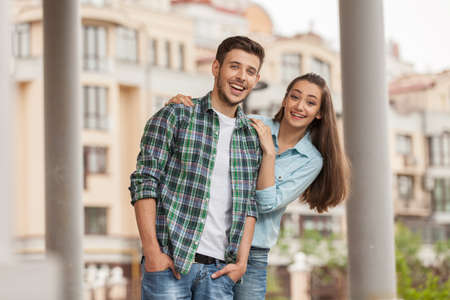 Cheerful young couple standing on city street. beautiful girl huging guy from behind holding hands in pocket photo