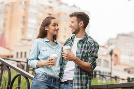 Young couple drinking coffee outside. Portrait of happy partners having break outside at summer  Stock fotó