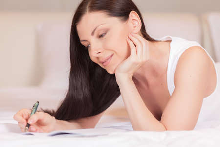Girl writes diary while lying in bed in morning. beautiful brunette resting in bed and writing letter