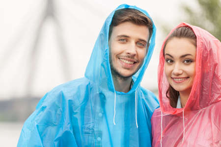 Pretty young woman in red raincoat. young couple wearing raincoat and smiling  photo