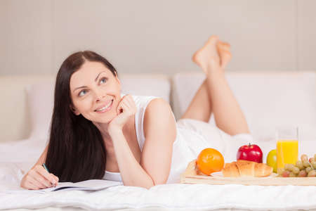 woman lying in bed: Girl writes having breakfast in bed in morning. beautiful brunette resting in bed and writing letter