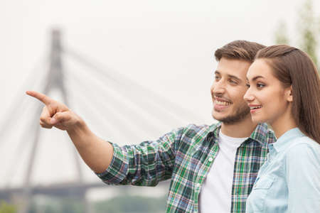 handsome man showing pretty girl. woman looking at man pointing far and smiling photo
