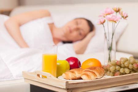 desayuno romantico: Mujer hermosa con el desayuno en la cama temprano. mujer durmiendo en la cama en la almohada blanca Foto de archivo