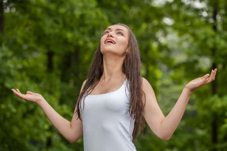 lifted hands: Happy young woman enjoying rain in summer. Woman standing under rain and arms raised Stock Photo