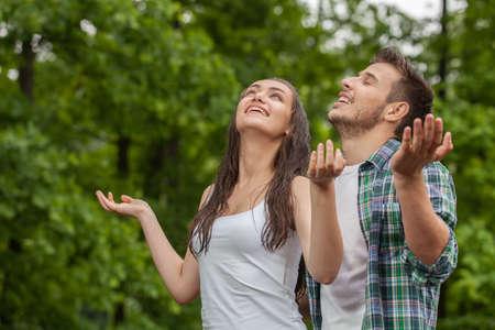 mojado: Mujer joven feliz disfrutando de la lluvia en verano. La mujer y el hombre de pie bajo la lluvia y los brazos levantados