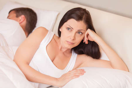 nude wife: unhappy woman lying in bed stressed. couple having problem while man sleeping Stock Photo