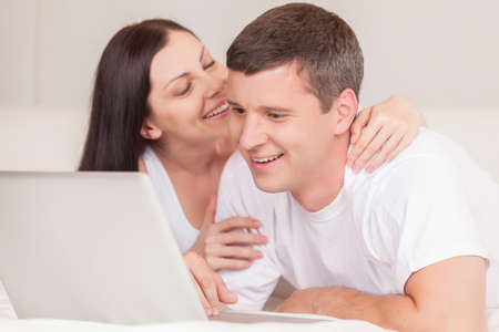 happy couple with laptop in bed smiling. couple with laptop watching movie on computer photo