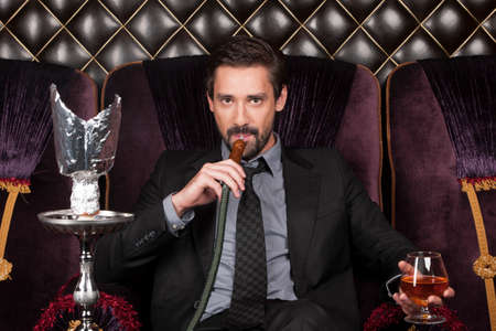 inhaling: man sitting and inhaling shisha in restaurant. handsome businessman looking into camera and drinking Stock Photo